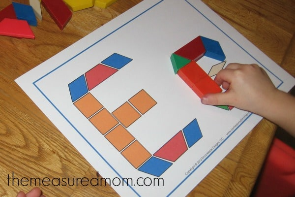 child building the letter E with blocks