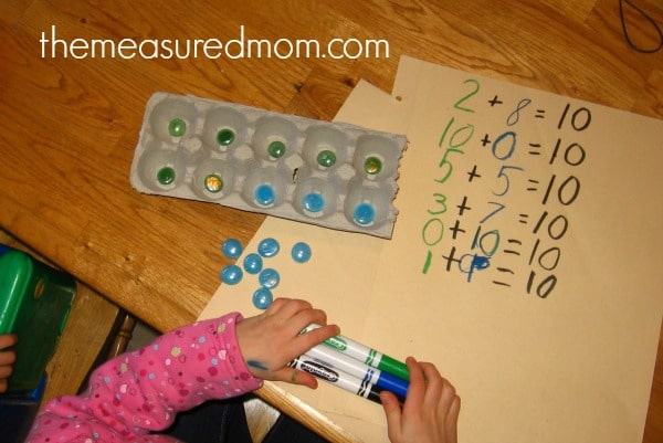 child practicing counting with gems