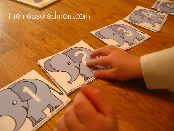 child practicing counting with numbered elephant cards