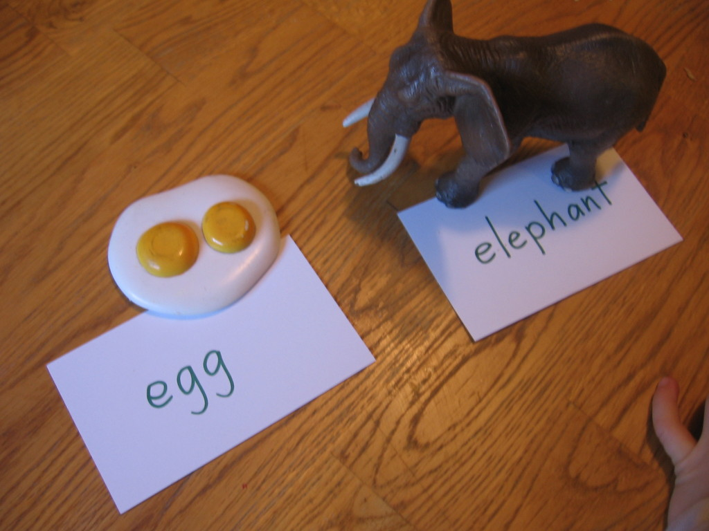 child sorting toy egg and toy elephant