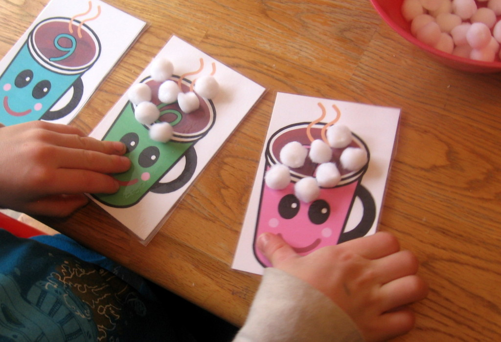 children placing marshmallows on cards