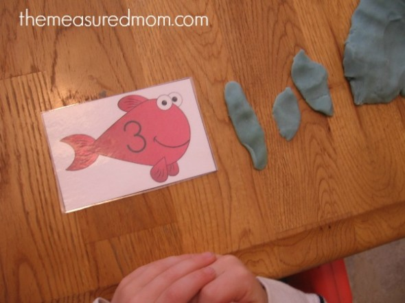 child making playdough worms for fish card