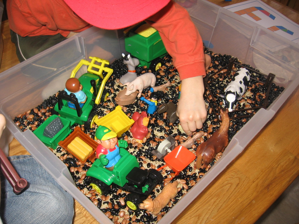 children playing in beans and rice box