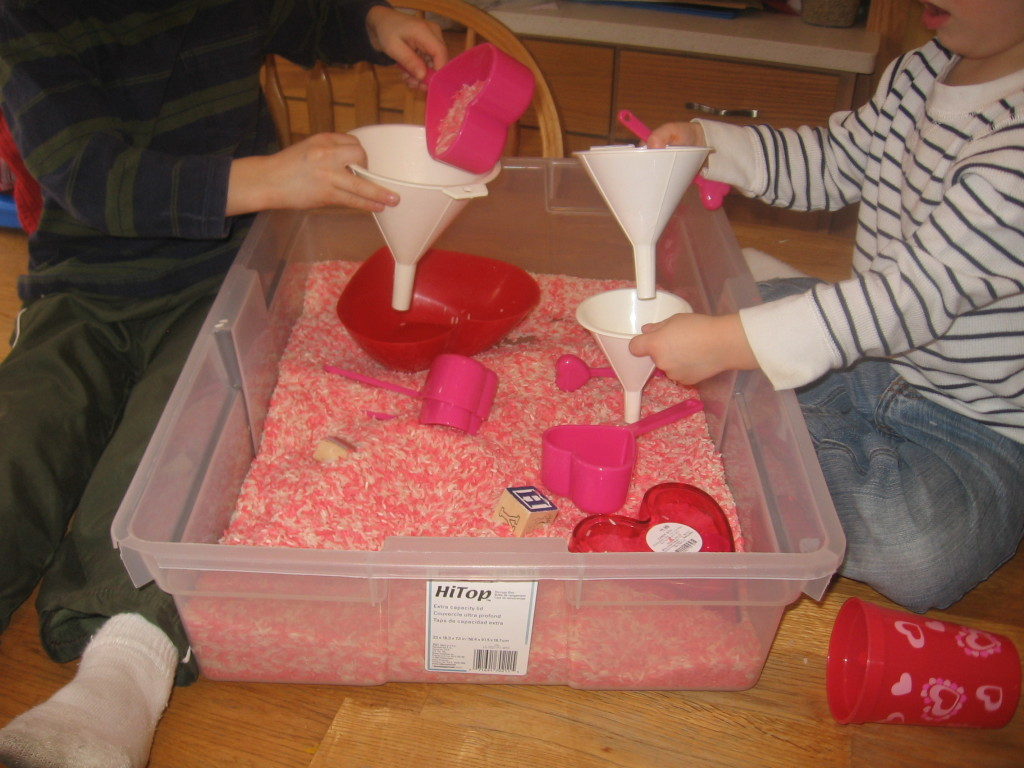 children dumping rice into funnels