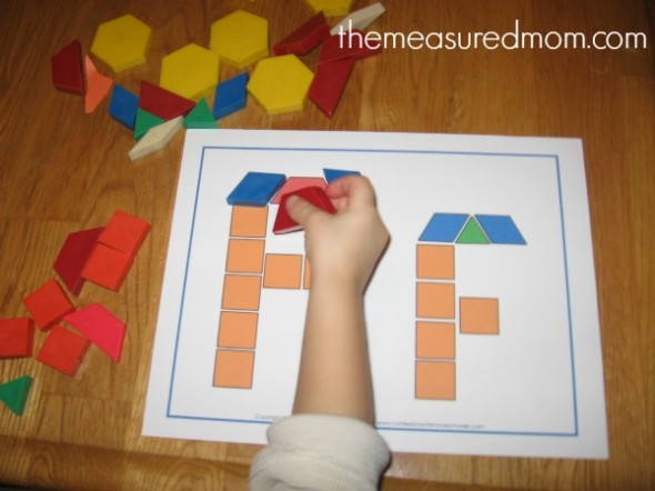 child placing shapes on block letter F card