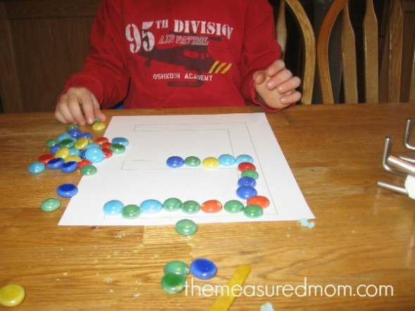 child placing gems into block letter E