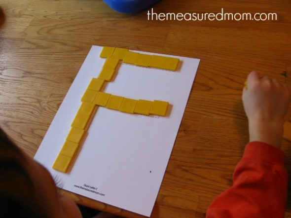 child placing tiles on block letter F