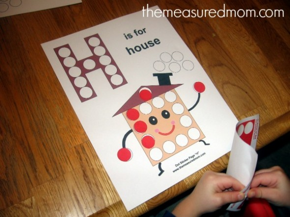 child putting stickers on letter H worksheet