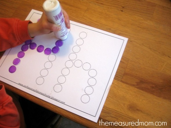 child putting dots on letter H worksheet