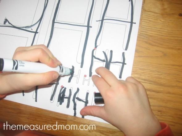 child writing on letter H worksheet