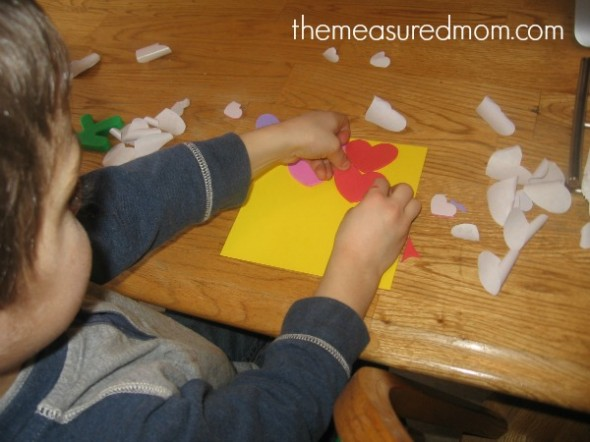 child placing heart stickers on paper