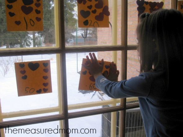 child placing paper on window