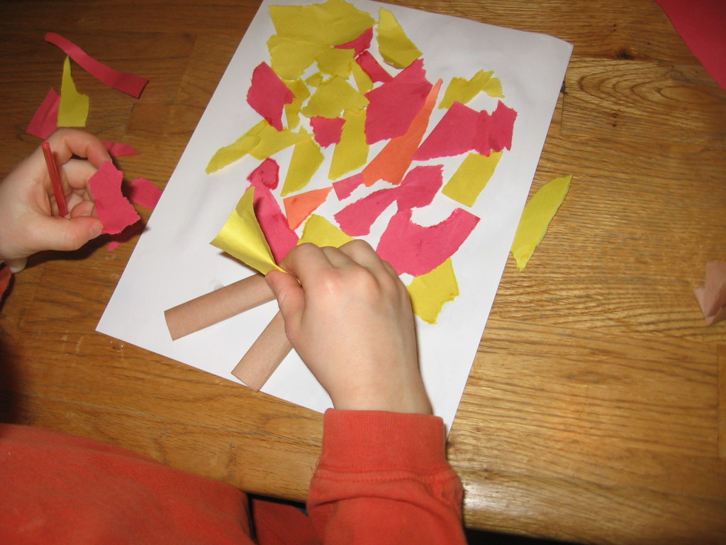 child placing colored paper on paper