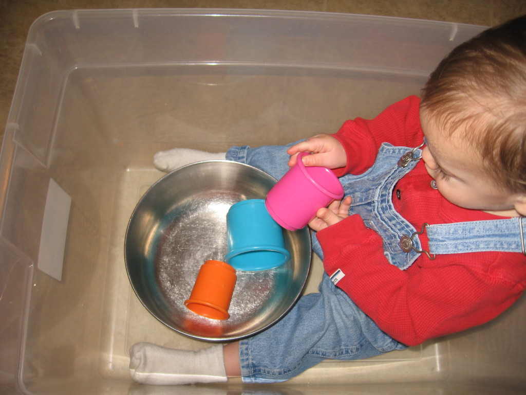 baby playing with cups in box