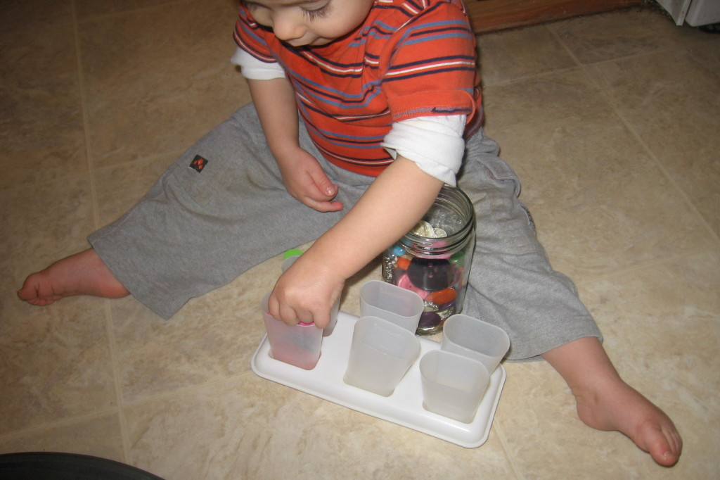 child placing button into popsicle mold