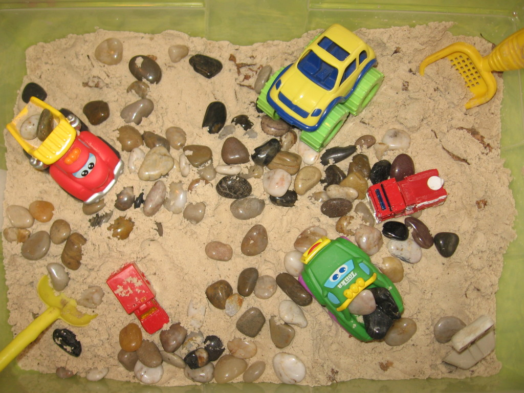 sandbox with cars, rocks, and sand toys