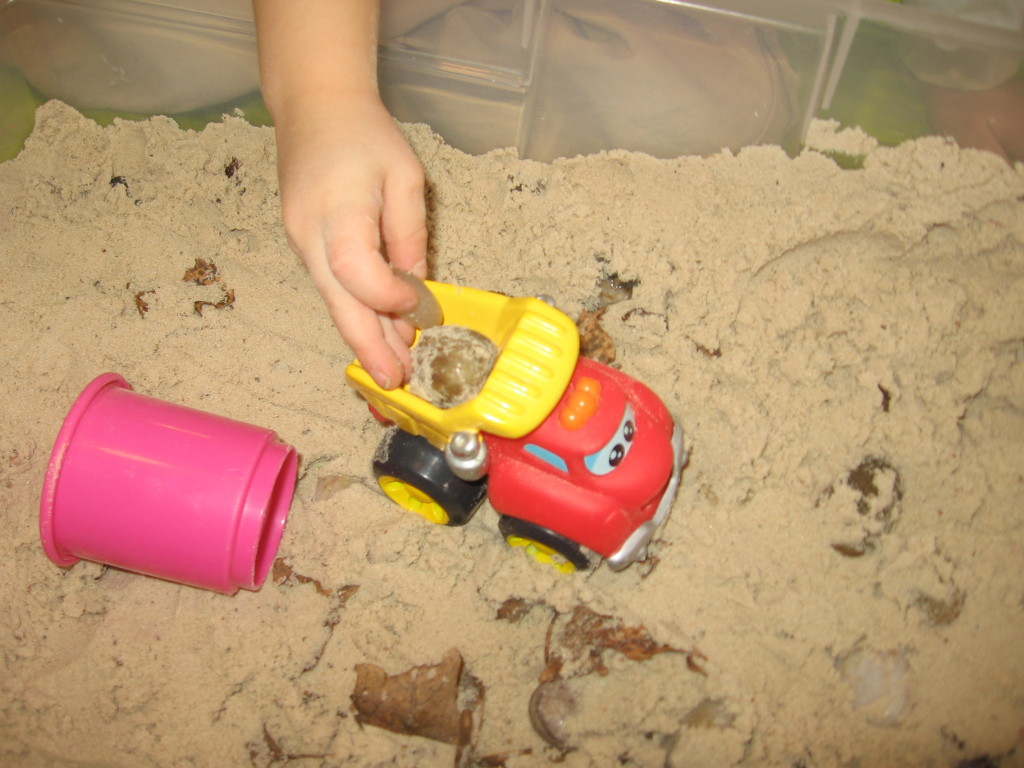 child driving toy truck in sandbox