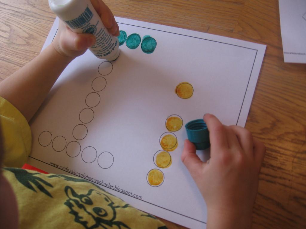 child stamping Do-A-Dot marker on letter I worksheet