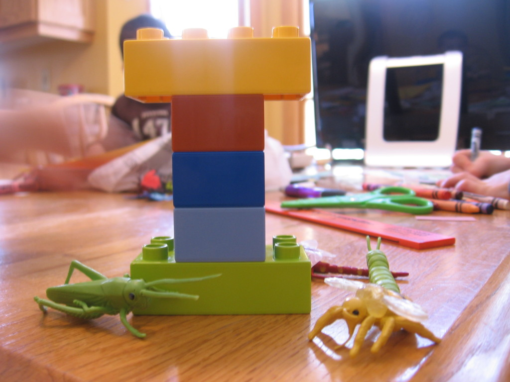 letter I made out of Duplos with toy insects