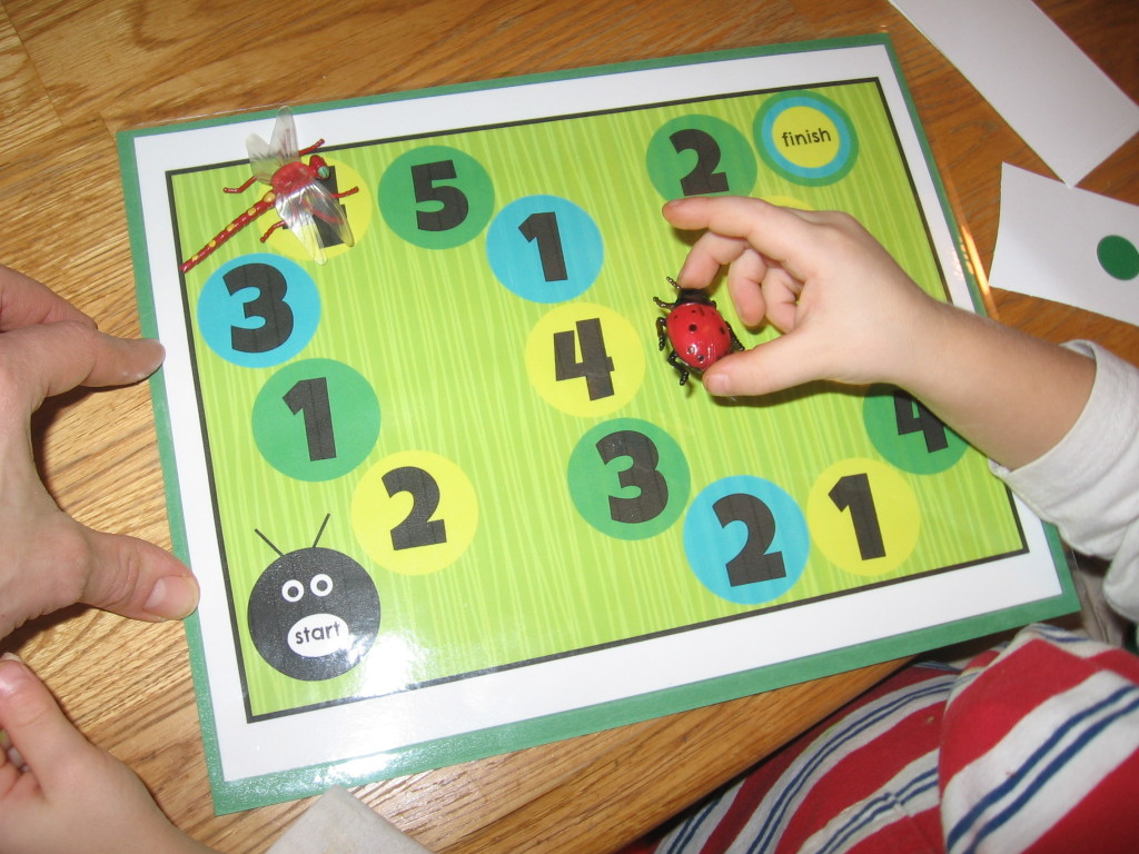 child placing toy bug on counting mat
