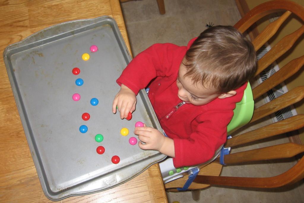 child placing magnets on baking sheet