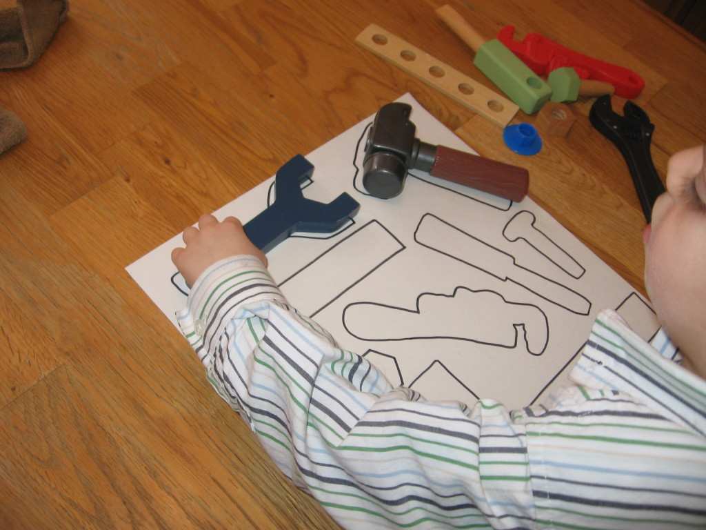 child placing toy tools on paper
