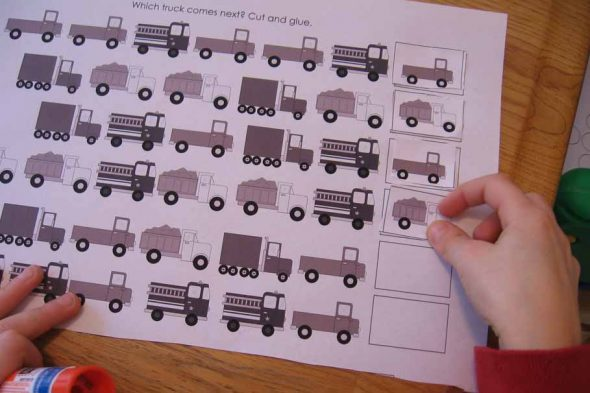 child placing card on truck pattern strips