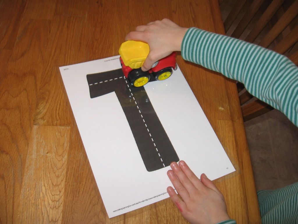 child with highway ABC card (letter T)