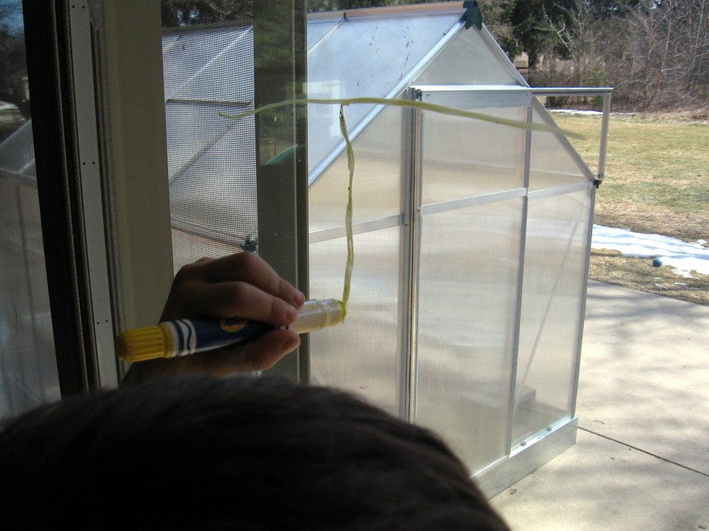 child writing on window making letter T with Crayola window crayons
