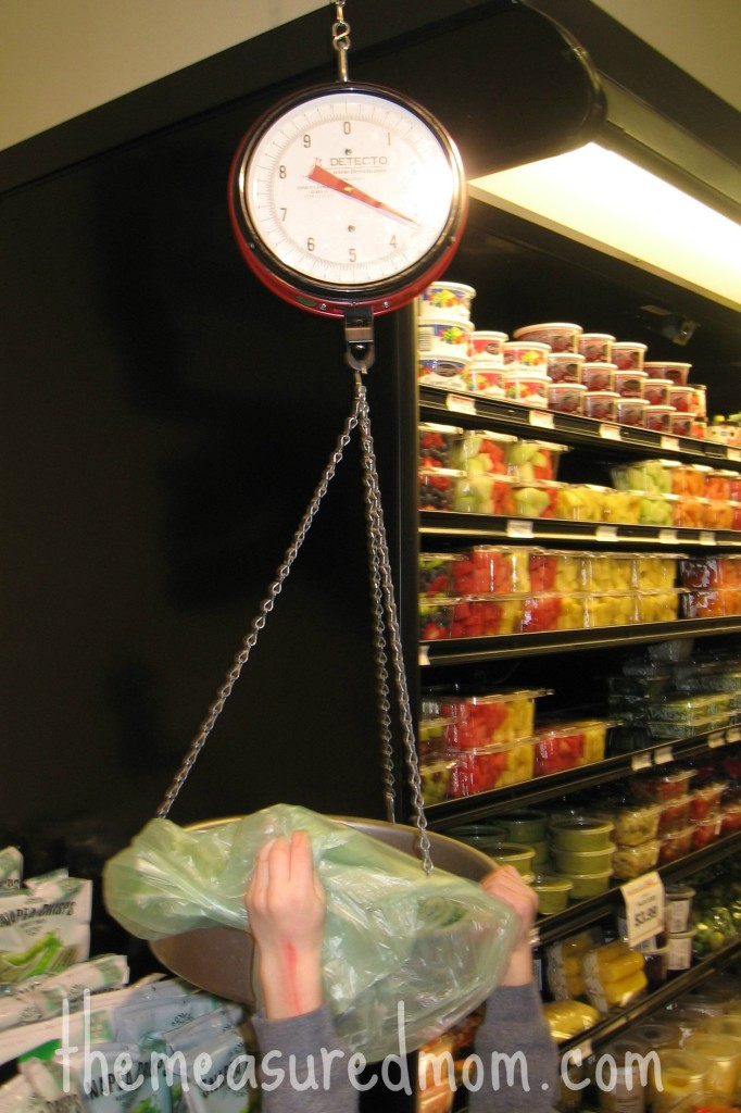 child putting something on grocery store scale