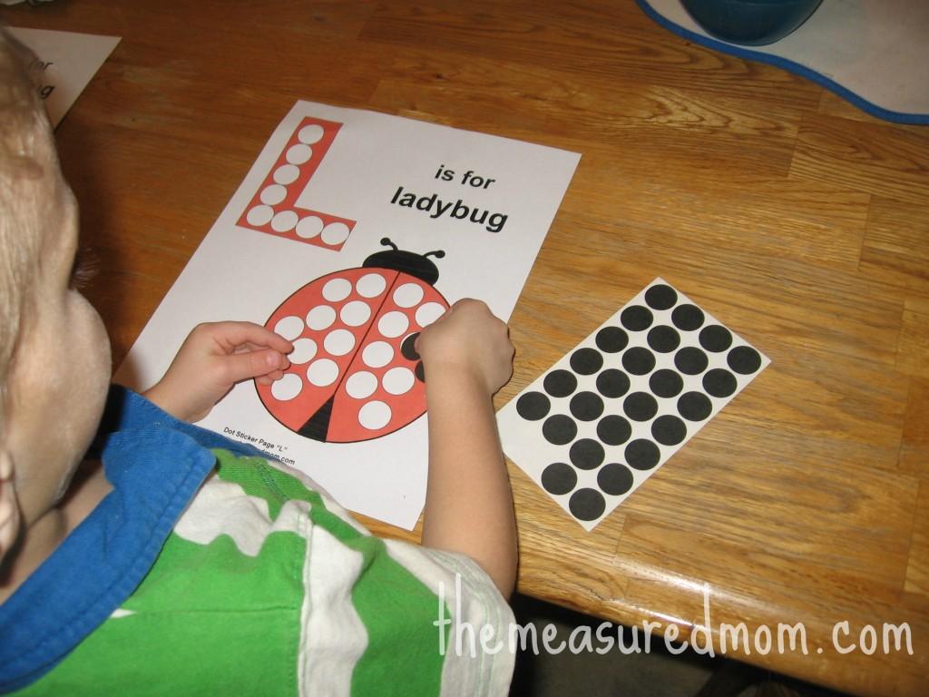 child placing dot sticker on letter L worksheet