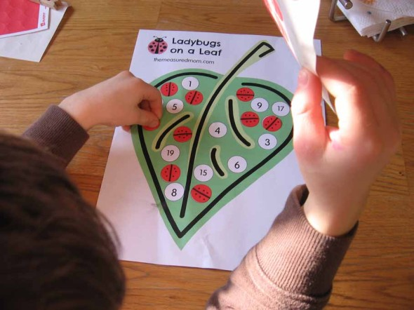 child placing sticker on clip art of leaf
