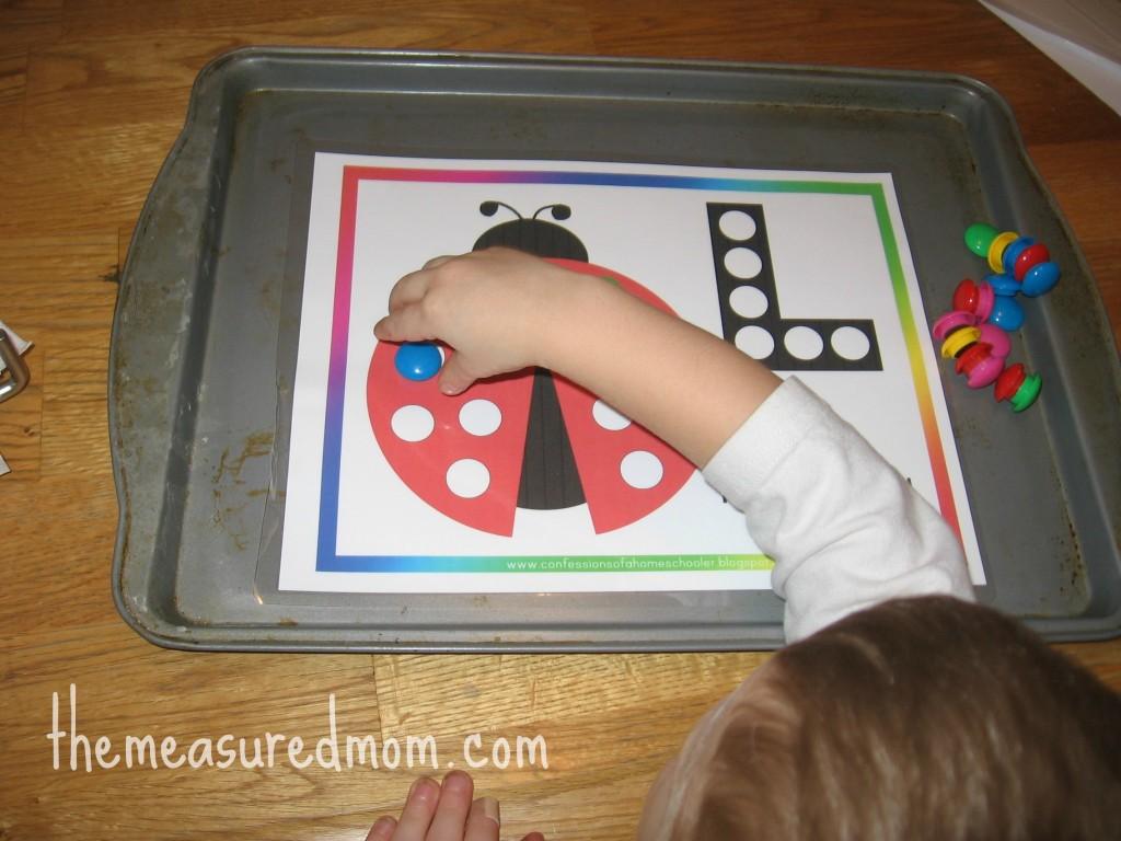 child placing magnet on letter L worksheet