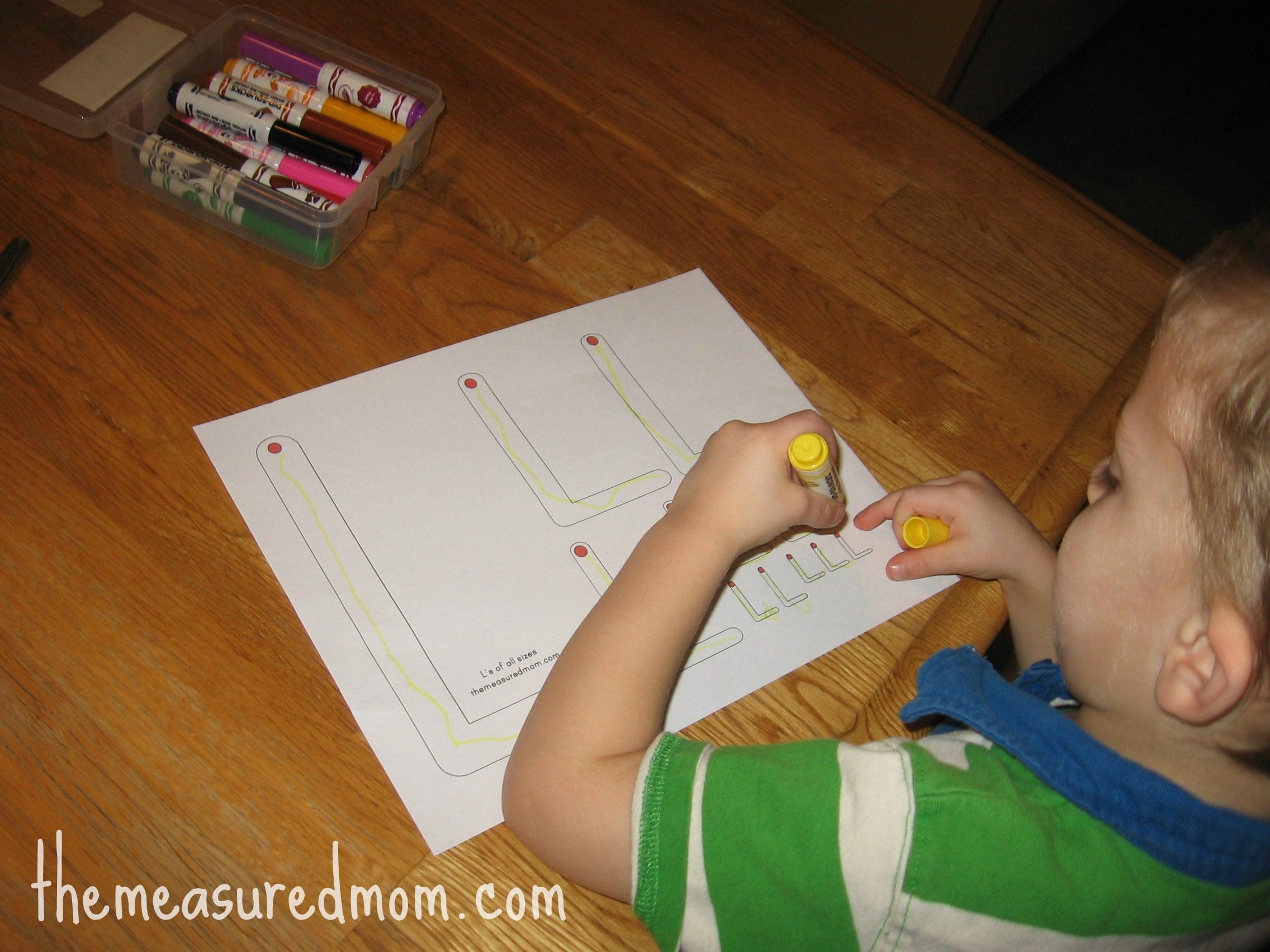 child forming L's on letter L worksheet