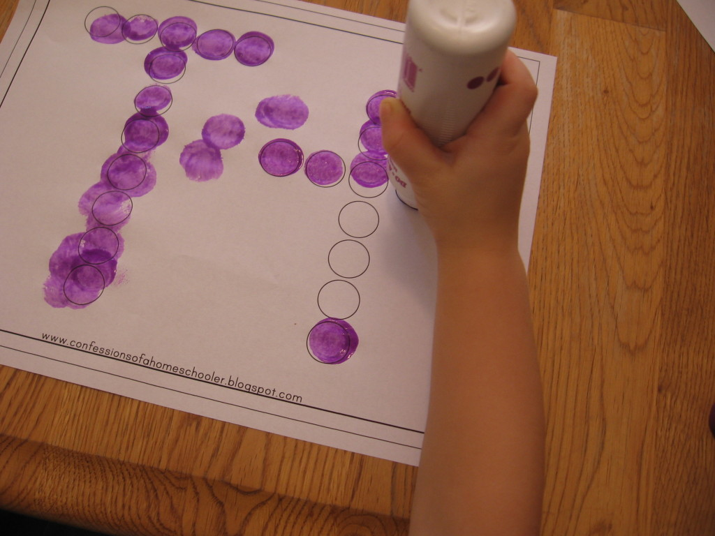 child stamping Do-A-Dot marker on letter T worksheet