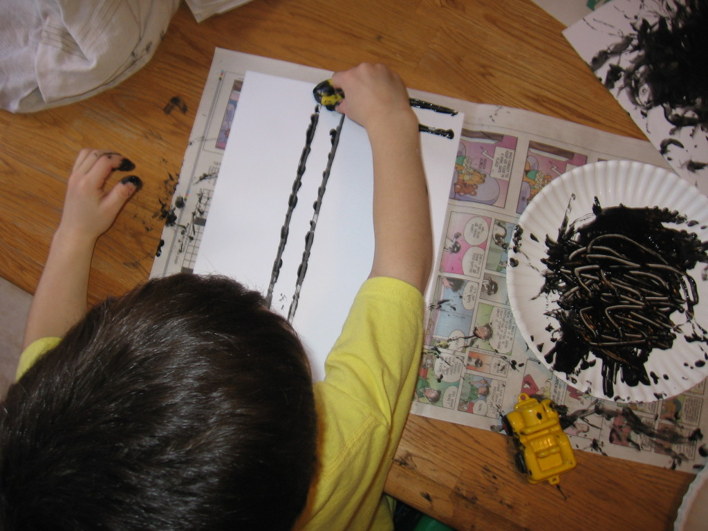 child making letter T with tire tracks