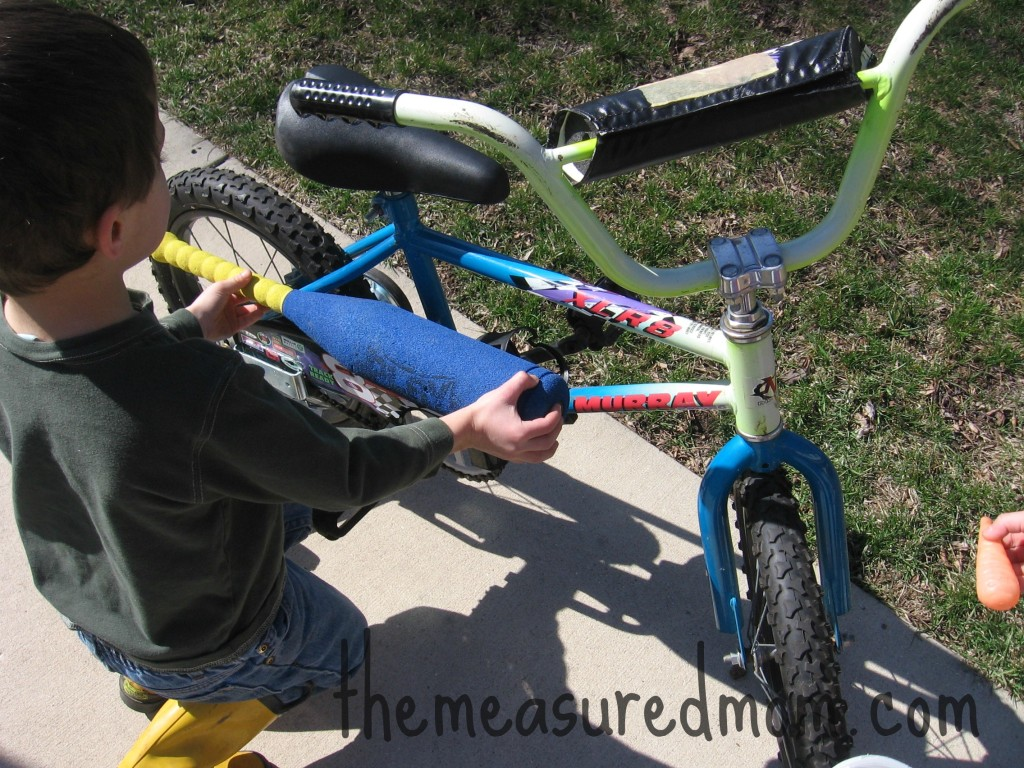 child comparing baseball bat to bike