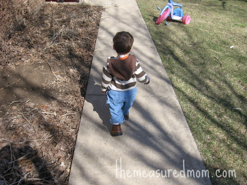 child walking on sidewalk