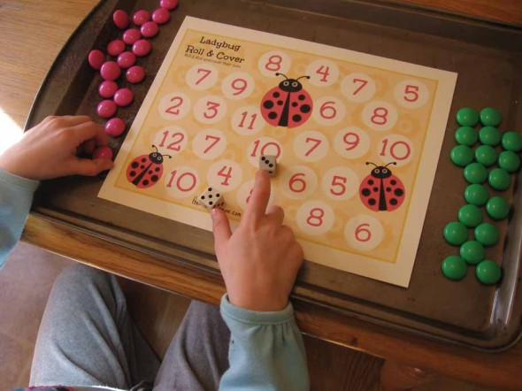 child playing ladybug roll and cover addition game
