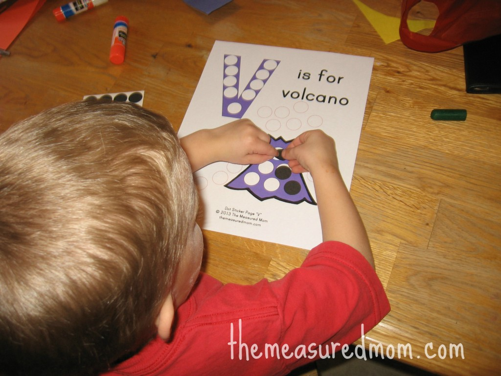 child placing dot stickers on V is for volcano worksheet