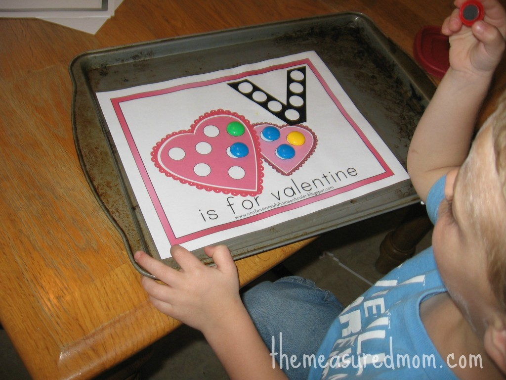 child placing magnets on V is for valentine worksheet