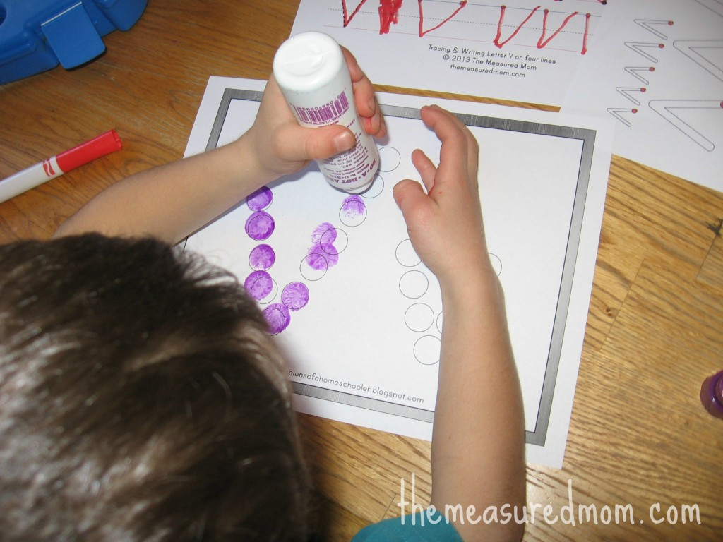 child stamping Do-a-Dot marker on V worksheet