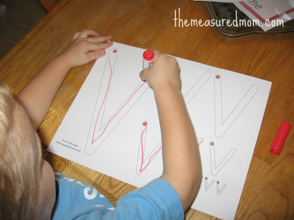 child writing on V worksheet