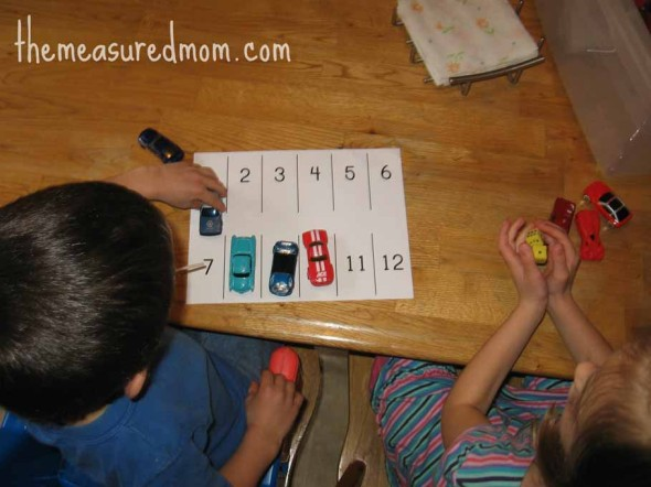 children rolling dice and parking cars