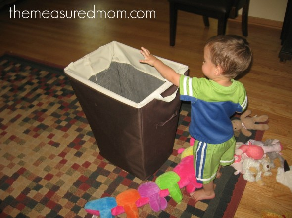 child tossing stuffed animals into hamper