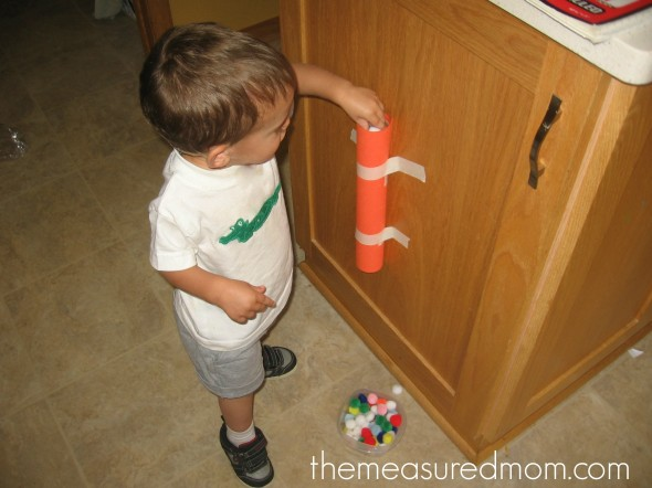 child poking pom-poms through a paper towel tube