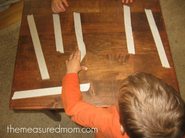 child placing masking tape on table