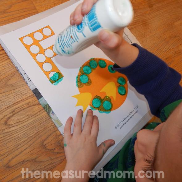 child stamping do-a-dot marker on letter F worksheet