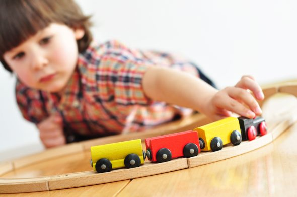 Little boy playing with a toy train